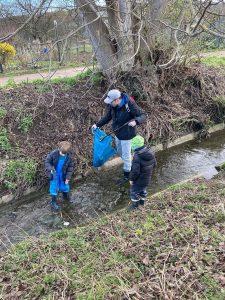 Abbildung: Ein Vater sammelt mit Kindern Müll an einem Bach bei Koblenz